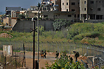 Backdropped by the Druze village of Majdal Shams, Golan Heights, Israeli soldiers  make their way at Israel-Syria border, a day after deadly protests that marked the 44th anniversary of the 1967 Six-Day War.