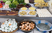 Duck breasts, battered fish and preserved '1000 year old' eggs, at food stall in Fengdu, China