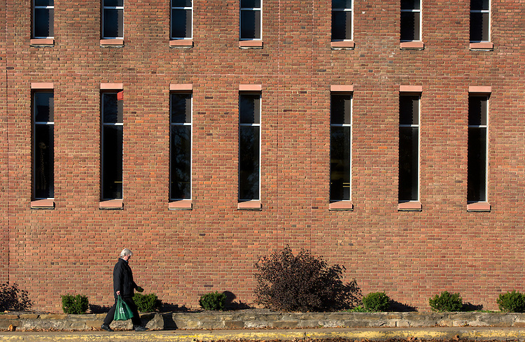 A pedestrian walks beside Alden Library on Ohio University's Athens campus on November 12, 2016.