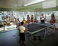 People playing ping pong in the motel game room.