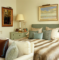 The small but attractive bedroom is furnished in a contemporary style and the bed is covered in a faux fur