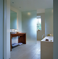 The contemporary bathroom is built of glass and limestone and has a tiled wet room at the far end