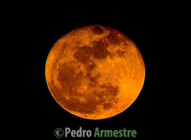 A perigee moon rises above the Almudena Cathedral in Madrid on March 20, 2011. A perigee moon is visible when the moon's orbit position is at its closest point to Earth during a full moon phase (C) Pedro ARMESTRE