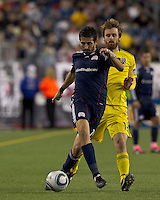 New England Revolution midfielder Monsef Zerka (19) dribbles as Columbus Crew midfielder Eddie Gaven (12) pressures. In a Major League Soccer (MLS) match, the Columbus Crew defeated the New England Revolution, 3-0, at Gillette Stadium on October 15, 2011.