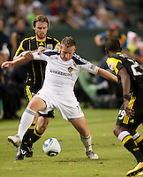Galaxy midfielder Chris Birchall (11) works the ball between Columbus Crew players Eddie Gaven (12) and Shaun Francis (29) during the second half of the game between LA Galaxy and the Columbus Crew at the Home Depot Center in Carson, CA, on September 11, 2010. LA Galaxy 3, Columbus Crew 1.