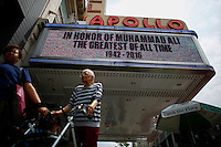 NEW YORK CITY, NY - JUNE 4: People walk in Harlem as Muhammad Ali's death news is display on screens at the Apollo theater on June 4, 2016 in Manhattan, New York. Ali died at a Phoenix-area hospital, where he had spent the past few days being treated for respiratory complications. Photo by VIEWpress
