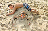 Two boys on the beaches of Dauphin Island, Alabama, a barrier island located three miles south of the mouth of Mobile Bay in the Gulf of Mexico. This island, which is approximately 14 miles long and less than two miles wide, appears to have fully recovered from the impact of Hurricane Katrina (2005) and the BP Deepwater Horizon Oil Spill in 2010. Both events greatly reduced tourism income (fewer people came to the island) and local business owners say many establishments went out of business. Today they say they're looking forward to a rebounding tourism business.