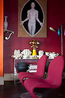 """In the small salon, furnished with a pair of Verner Panton chairs, a collection of Fulham Pottery created for the florist Constance Spry is displayed beneath a canvas """"Rebis"""" by Matthew Stradling"""