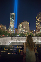 The Tribute in Light is seen behind the 9/11 Memorial waterfalls and reflecting pool in New York on September 11, 2014 for the13th anniversary of the September 11, 2001 terrorist attacks. The 88 high intensity lights that comprise the tribute create two vertical columns of light as a commemoration of the Twin Towers and the lives lost in the the 2001 attacks. (© Richard B. Levine)