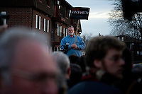 A Santorum supporter stands on the periphery as former senator Rick Santorum speaks to a crowd made primarily of media and protestors outside Belmont Hall and Restaurant in Manchest, New Hampshire, on Jan. 6, 2012.  Santorum is seeking the 2012 GOP Republican presidential nomination.  Protestors were primarily from the Occupy New Hampshire group..