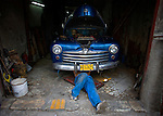 cuban mechanic working on chevy in cuban auto shop