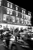 Traffic blurs as it passes by the Hotel Continental at night in Saigon.