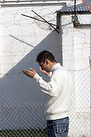 South America, Argentina, La Plata, Los Olmos. Freedom Behind Bars, Prison and Divinity - An inmate lifts his hands in prayer in Unit 25 of Los Olmos Prison. Los Olmos Prison is one of the principal security prisons in Argentina. It hosts Unit 25, also known as Christ the Only Hope Prison Church, one of the largest prison churches worldwide. The transformation of criminals into the God fearing and leading them to the Lord has taken hold, not only in the lives of inmates, but also in inmate families and prison guards. Once the countries worst killers and thieves have since become spiritual leaders to other criminals, creating a revolutionary spiritual rehabilitation, July 2006 &copy; Stephen Blake Farrington<br />