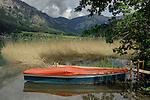 Orange tarpaulin covering rowing boat.Lake Haldensee, Nesslewangle, Reutte district. Austria.The Alps