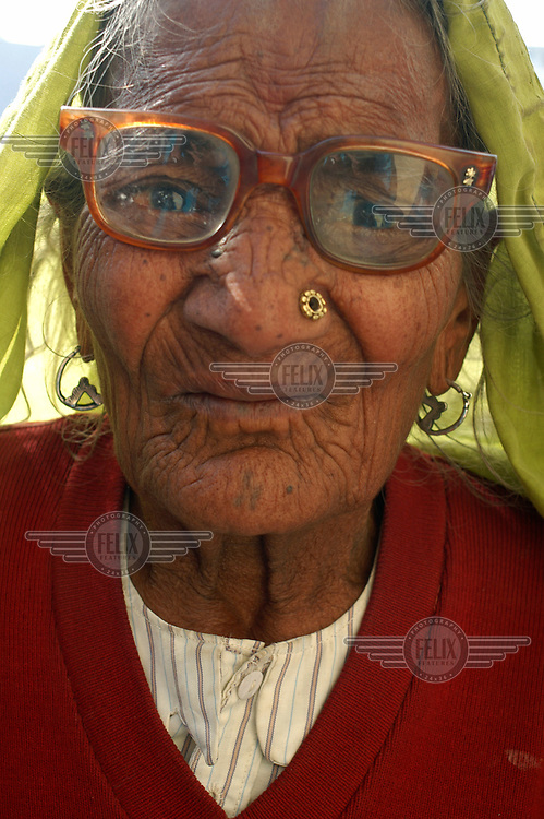 An elderly woman with broken glasses.