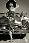 A model wearing a large hat and a spotted dress leaning on a 50's US car and soldier