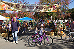 Children on bikes and other guests walk near the Children's Alley.