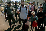 "Michael Po'eh and his family are evacuated by Israeli policemen from ""Palm Beach"" hotel, in the Israeli settlement bloc of Gush Katif, Gaza Strip. Hardliners from the West Bank have taken-over the hotel, setting it as their base for future struggle against Israel's upcoming pullout from Gaza. They renamed it to ""Ma'oz Hayam"" outpost."