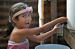 Heart Bigay, 6, gets clean water from a water filter in her family's temporary home in Tanauan, a city in the Philippines province of Leyte that was hit hard by Typhoon Haiyan in November 2013. The storm was known locally as Yolanda. Hundreds of families here received water filters from the United Methodist Committee on Relief, a member of the ACT Alliance. UMCOR is also working with city officials to help residents here build permanent houses to replace those they lost in the storm.