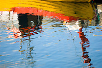 Reflection of a yellow fishing boat in the Reykjavik harbor, the capital of Iceland.