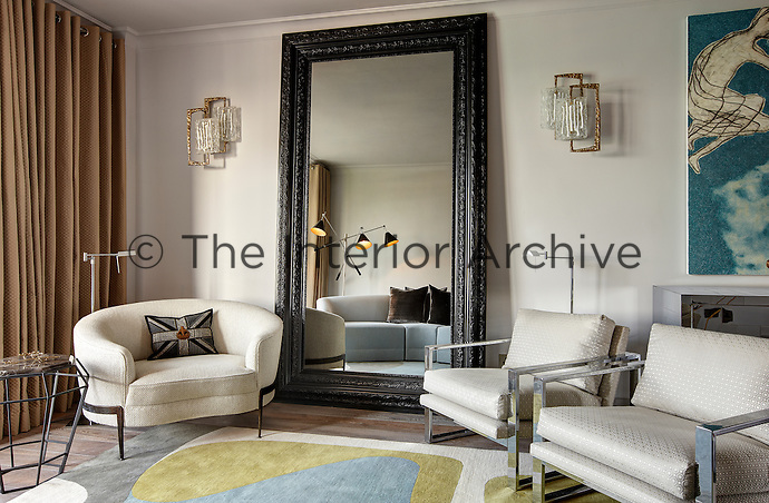 A stylish living room with a pale blue patterned rug and floor length curtains. The room is furnished with a oversize mirror propped against one wall, a tub chair and two armchairs with shiny steel frames and upholstered in a neutral fabric.