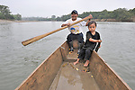 Accompanied by his son Juan, Crisanto Pop Ax steers his launch down the Salinas River at Santa Elena, in Guatemala's Peten region. Here the river forms the border between Guatemala and Mexico.