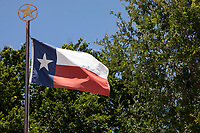 Texas Flag waving in the wind and Lone Star emblem on top of the flag pole.