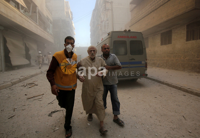 A civil defence worker helps a Syrian man following an air strike by government forces on the al-Mowasalat neighbourhood of the northern Syrian city of Aleppo on September 20, 2015. Photo by Ameer al-Halbi