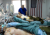 Spc. Jacob Coppess, 23 of Anderson, IN, tends to Pfc. Tyson Ivie, in the Intensive Care Unit of the Ibn Sina 10th Combat Support Hospital (CSH) in Baghdad. Ivie, a soldier with the 1st Battalion, 502 Infantry, 101st Airborne Division had shrapnel removed from his chest. March, 10, 2006. (James J. Lee / Army Times)