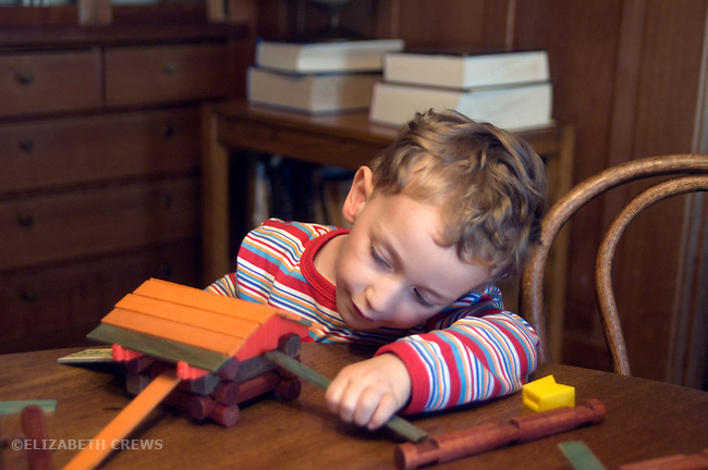 Berkeley CA Boy, two and a half-years-old absorbed in building with class Lincoln Logs construction toy  MR
