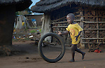 Andiru Gordon rolls a bicycle tire. The three-year old boy lost his father to the fighting that broke out in his home town of Bor, South Sudan, in December 2013, and along with his mother and five siblings moved to a camp for internally displaced people and then eventually to live with relatives in the town of Mundri.