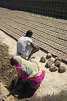 Indian family forming bricks made from mud clay at Khore Bricks Factory, Rajasthan, Northern India