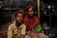 Alamgir and his mother at his mother's house. His mother is remarried and living with her second husband. Alamgir ran away from home 6 years ago from his home due to domestic violence and poverty. As per his version his father was a drunkard and used to beat his mother for no reason. His father even could not earn enough money to buy food for their big family. Due to this traumatic situation he ran away from house at the age of seven. Ever since, the Sealdah railway station in Kolkata has been his home. As far as company is concerned, he had not much reason to miss his family. There are around 500 children, from 5 to 16 years, who live in the premises of Kolkata's second largest train terminus. Most of them addicted to Brown Sugar and sniffing industrial adhesive Dendrite. They say they don't feel hungry if they take the drugs. Their presence is conspicuous, even in a place that registers an average footfall of 1.4 million on weekdays. Their activities cover a wide range, from begging, to pulling handcarts, to petty theft, to selling odds and ends on the platform or on trains. The money, earned or ill-gotten as the case may be, is spent in procuring heroin, brown sugar, cocaine, and tubes of Dendrite. Calcutta, West Bengal, India. Arindam Mukherjee