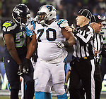 Seattle Seahawks defensive end Cliff Avril (56) and  Carolina Panthers guard Trai Turner (70)  are held apart by Head Linesman Derrick Bowers (74) in the NFC Western Division Playoffs at CenturyLink Field  on January 10, 2015 in Seattle, Washington. The Seahawks beat the Panthers 31-17. ©2015. Jim Bryant Photo. All Rights Reserved.