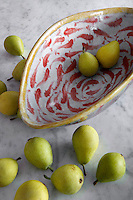 Fresh pears from a contemporary pottery bowl cover the marble worktop in the kitchen