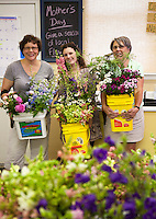 Suzanne Frye, Annie Holt, and Lisa Ziegler holding buckets of hardy annual flowers for wedding bouquets grown at local flower farm The Gardeners Workshop, Newport News, Virginia