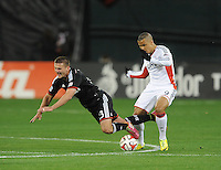 Washington D.C. - April 5, 2014: Perry Kitchen (23) of D.C. United gets fouled by Charlie Davies from the New England Revolution.  D.C. United defeated 2-0 the New England Revolution during a Major League Soccer match for the 2014 season at RFK Stadium.