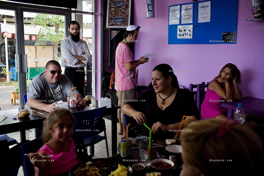 Barry (4th from left) puts Teffilin twice a week with Rabbi Goldshmid (3rd from left), in his Thai/Israeli cuisine restaurant which was opened 8 months ago. He has been living in Koh Samui for 11 months now and used to work as a restaurant manager in a Thai restaurant in China Town, Israel. Photo by Suzanne Lee / For Chabad Lubavitch
