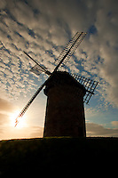 The rising sun back lights the windmills of Ireland. Skerries, Ireland