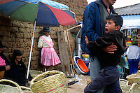 "A boy yawns in his father's arms in the local produce market in Vallegrande, Bolivia Sunday, Nov. 14, 2004. Ernesto ""Che"" Guevara was captured by the Bolivian army in 1967 in a nearby valley and executed in La Higuera days later. His body was put on public display in the laundry room of the Vallegrande hospital, then secretly buried under the air strip for 30 years. Guevara and fellow communist guerillas were attempting to launch a continent-wide revolution modeled on Guevara's success in Cuba in the late 1950s. The Bolivian government recently began promoting the area where he fought, was captured, killed and burried for 30 years as the ""Ruta del Che,"" or Che's Route. (Kevin Moloney for the New York Times)"