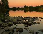 River rock in the shallows of the Spokane River near Stateline Idaho and reflections in the calm at twilight.