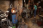 Blacksmith working preparing metal to be put back in furnace