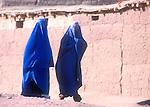 Two Afghan refugee women walk through the Shamshatoo refugee camp dressed in burkas..