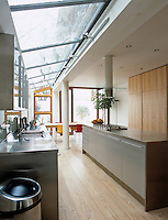 The contemporary stainless steel kitchen is open plan with the dining area and benefits from a skylight