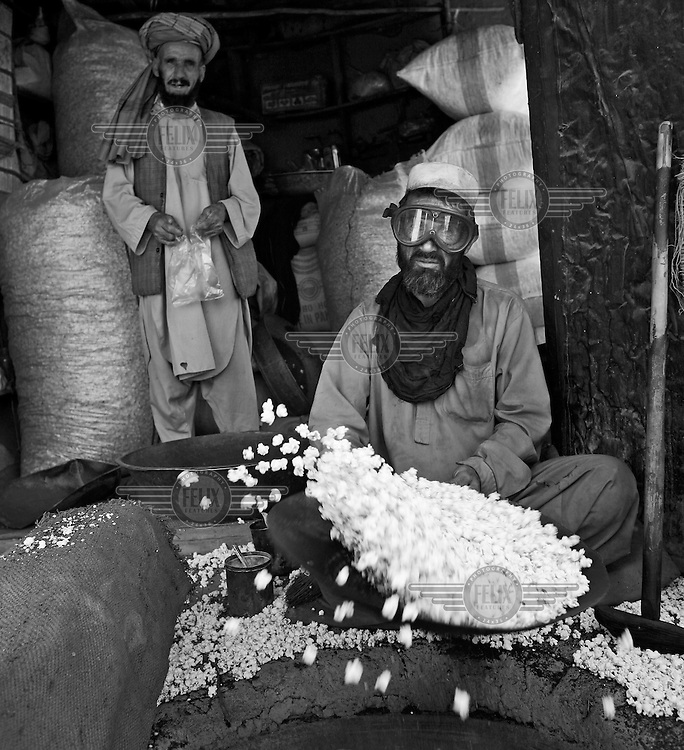 Popcorn makers in the Murad Khane market. The man actually making the popcorn wars goggles to protect himself from flying popcorn.