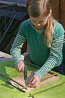 Kinder basteln ein Fensterbild mit Blüten, Mädchen nagelt Holzrahmen aus Haselbaumästen zusammen