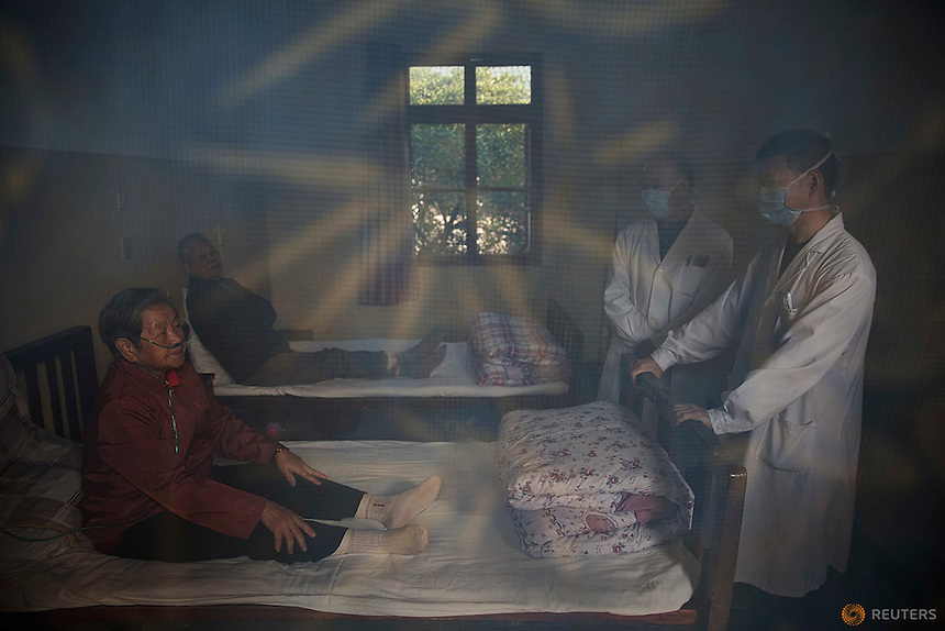 Fu Jianghua (R) and a member of his staff talk to patients with nasal cannulas for oxygen supplement in their room at Yangjia Hospital in Wuji County, China's Zhejiang Province October 19, 2015. Fu Jianghua, who works at Yangjia Hospital since 1983 when it was operated by a local mine is now its president. The hospital, once considered top medical institution with latest imported equipment became private after the mine company that built it went broke in 2001. Since that time the hospital is not able to keep the high standards and is now offering only basic care for its remaining patients.    REUTERS/Damir Sagolj