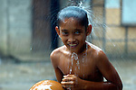 A boy in Mindanao washes under eave of house during rain shower.