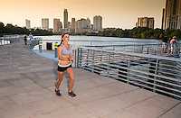 Attractive female runner runs on the the Boardwalk Trail along Lady Bird Lake, with a panoramic Austin Skyline background.