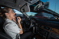 A businesswoman applies lipstick and talks on her smart phone while driving in I-35 rush hour Austin traffic.